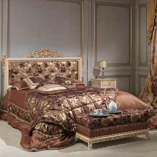 Bed with capitonné headbord and rich carvings handmade in Italy, laquered with gold details as the night tables. Capitonné bench