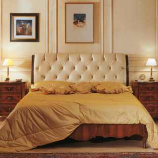 Luxury classic bed with capitonné leather headboard, walnut night table, antique finish